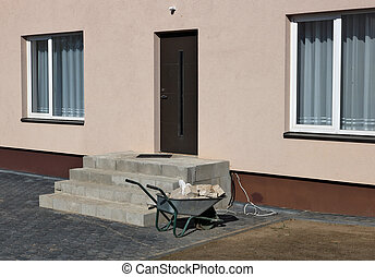 A wheelbarrow with stones near a rural house under construction.