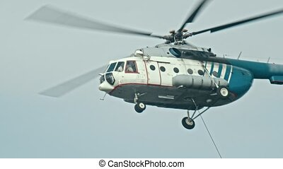 A white and blue helicopter flying in the sky at overcast weather - the cable hangs out of the helicopter