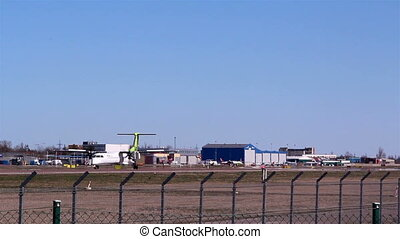 A white and green airplane on the airport