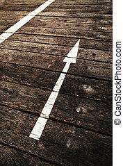 a white arrow upward on the wood