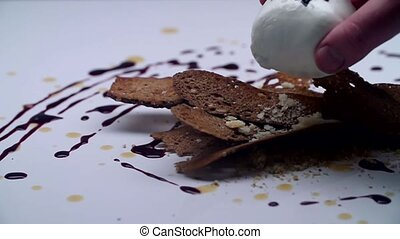 A white ball is laid over the black bread on a white table.