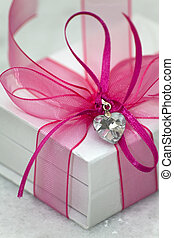 A white box tied with a pink satin