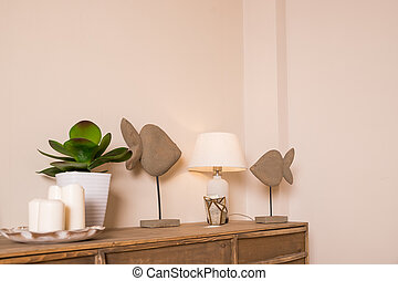 A white candles, lamp and a small potted plant are placed on the table in the bedroom. Candles, decor and green plant in white pot on the table in elegant stylish apartment. home decor. Interior design.