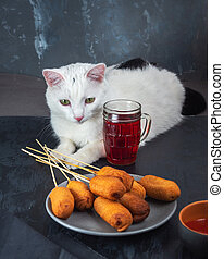 A white cat lies near a plate with sausages. On the table are sausages on a gray plate, ketchup