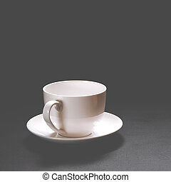 A white ceramic coffee cup stands on a black background