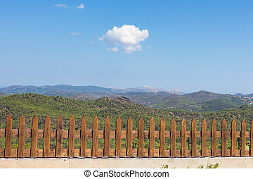 A white cloud in the blue sky above the green mountains behind the fence