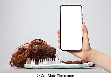 A white comb with false hair. White background. A female's hand holds a smartphone with a white screen. Mock up. The concept of buying and selling hair.