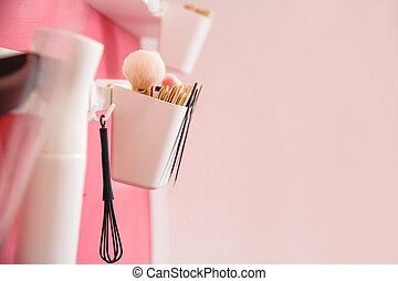 A white container with a close-up of the master's tools on a pink wall in a beauty salon.