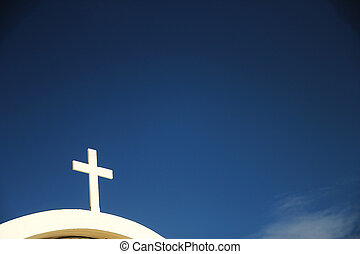 white cross of the church against the sky