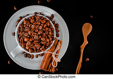 A white cup full of coffee beans stands on a white saucer, which stands on a black background