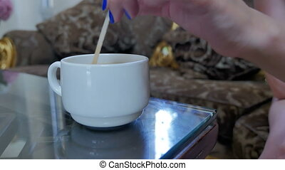 A white cup of coffee is on the table.