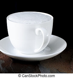 A white cup of coffee with a thick foam stands on a black table next to a multi-colored wild stone