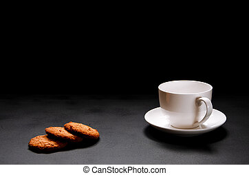 A white cup of coffee with homemade orange biscuits stands on black