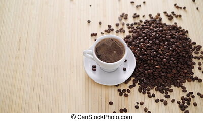 A white cup of evaporating coffee on the table with roasted beans