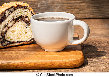 A white cup of hot coffee with bread on wooden background.