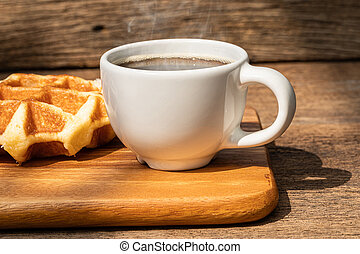 A white cup of hot coffee with waffle on wooden background.