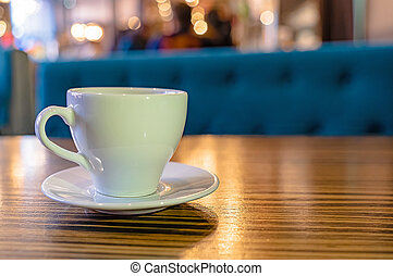 A white Cup of tea on a wooden table in a cafe close-up.