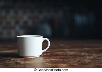 A white cup stands on a wooden table. Soft focus