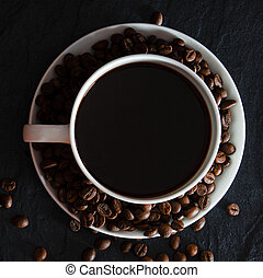 A white cup with black fragrant coffee stands on a black background