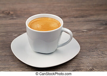 A white cup with coffee on a wooden background