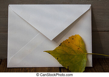 a white envelope and leaves on grey wooden background