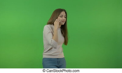 A white girl with long hair talks on a smartphone. On the green screen.
