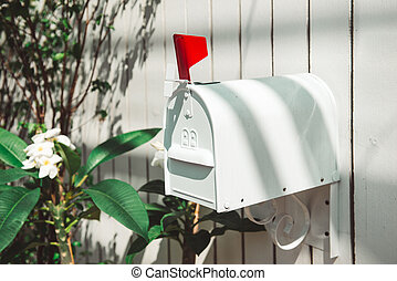 A white letterbox outside of the house