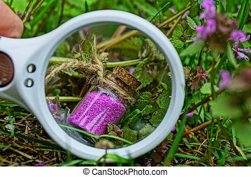 a white magnifier enlarges a small glass bottle with red sand among grass and flowers
