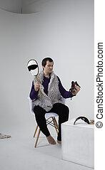 A white man is sitting in a chair. Holds the mask in his hands. On cyclorama
