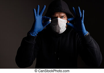a white man with a beard, wearing a medical mask and rubber gloves, demonstrates two pills for the disease