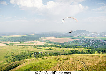 A white-orange paraglider flies over the mountainous terrain