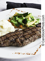 A white plate holds a delicious grilled New York Strip Steak with a side of mashed potatoes and fresh mixed vegetables. A napkin roll of utensils sits aside the plate.