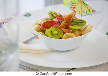 A white plate of fruit salad