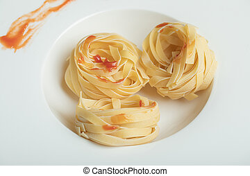 A white plate of uncooked nest noodles with red pepper