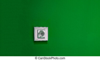 a white socket on the green wall