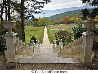 A white stone staircase in the autumn garden leads to the yellow autumn trees on a background of mountains with clouds