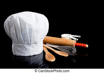 A white toque with cooking utensils including rolling pin, wooden spoons, wisk and measuring cups on a black background
