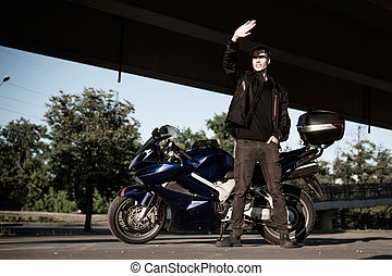 A white young man is standing next to a motorcycle.