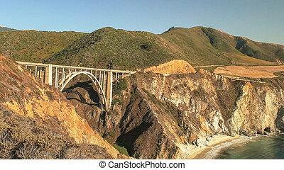 a wide angle shot of bixby bridge on highway 1 along the coast of big sur