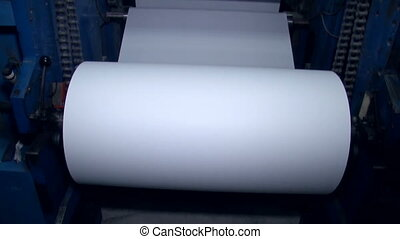 A wide paper roll is rotated on the machine for further cuts 2