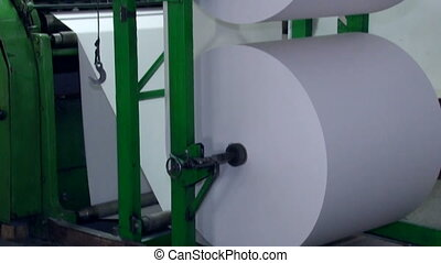 A wide paper roll is rotated on the machine for further cuts 5