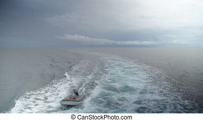 A wide shot of a mini boat on ocean