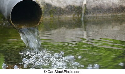 A wide tube with bubbling water falling into a lake in...