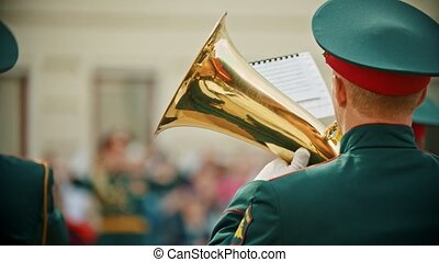 A wind instrument military parade - a man in army costume playing musical instrument outdoors. Mid shot
