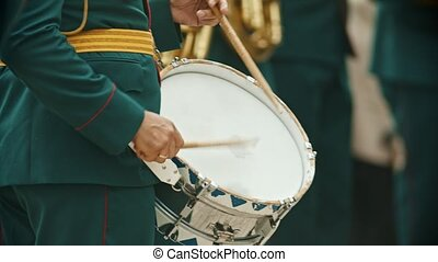 A wind instrument military parade - a person in green costume playing drums outdoors. Mid shot