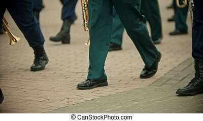 A wind instrument military parade outdoors - people in green costumes marching on the street holding instruments. Mid shot
