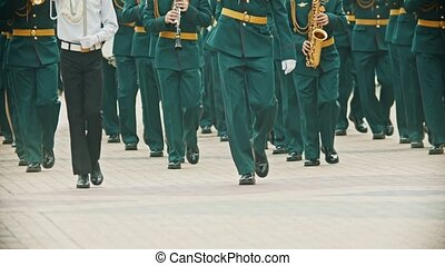 A wind instrument parade - military musicians in green costumes marching on the street holding musical instruments. Mid shot