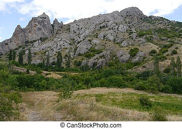 A winding steep rocky mountain with green trees and shrubs at its foothills
