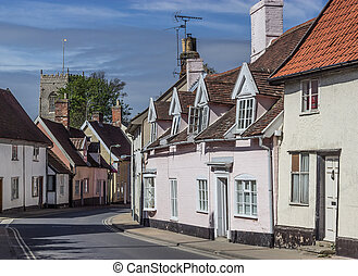 A winding street in Framlingham, Suffolk, UK, with traditional picturesque cottages.