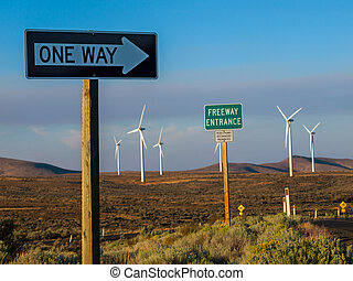 A Windmill Farm on a Mountain with One Way Signs Pointing to a Freeway at Dusk